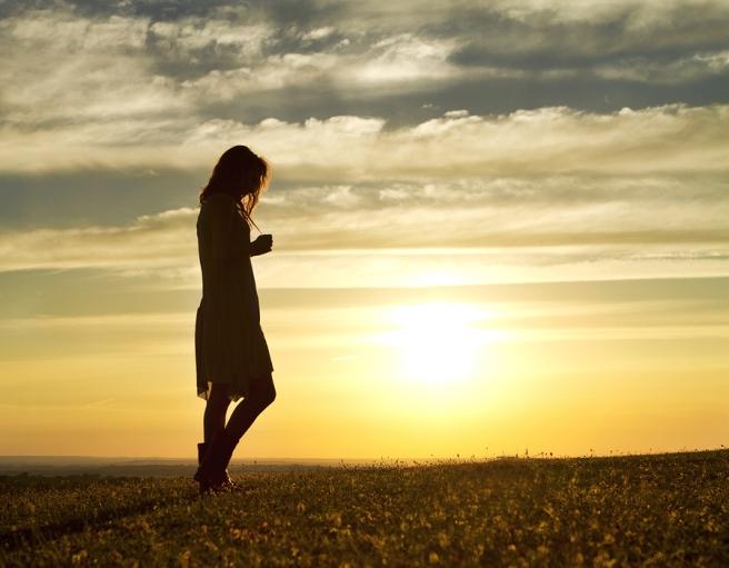 bigstock-Woman-walking-alone-at-sunset-52945624